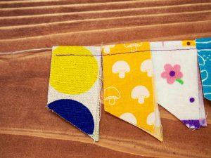 ②布を半分に折り間にひもを通しその下を縫います。好きな長さになるまで続けます。その後、裾をはさみで好きな形にカットして完成!
